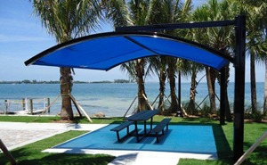 Curved square shade structure over park bench on waterfront.