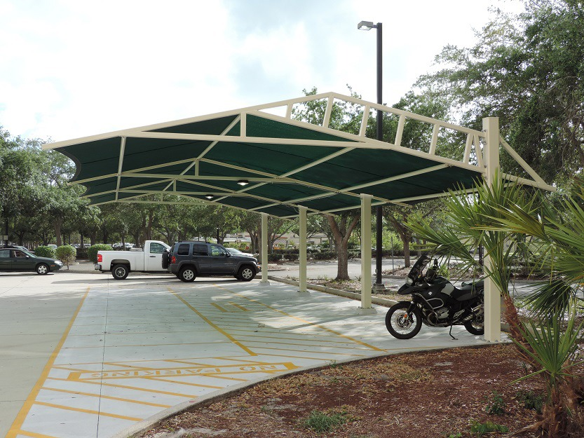 Bent square shade structure over parking lot row.
