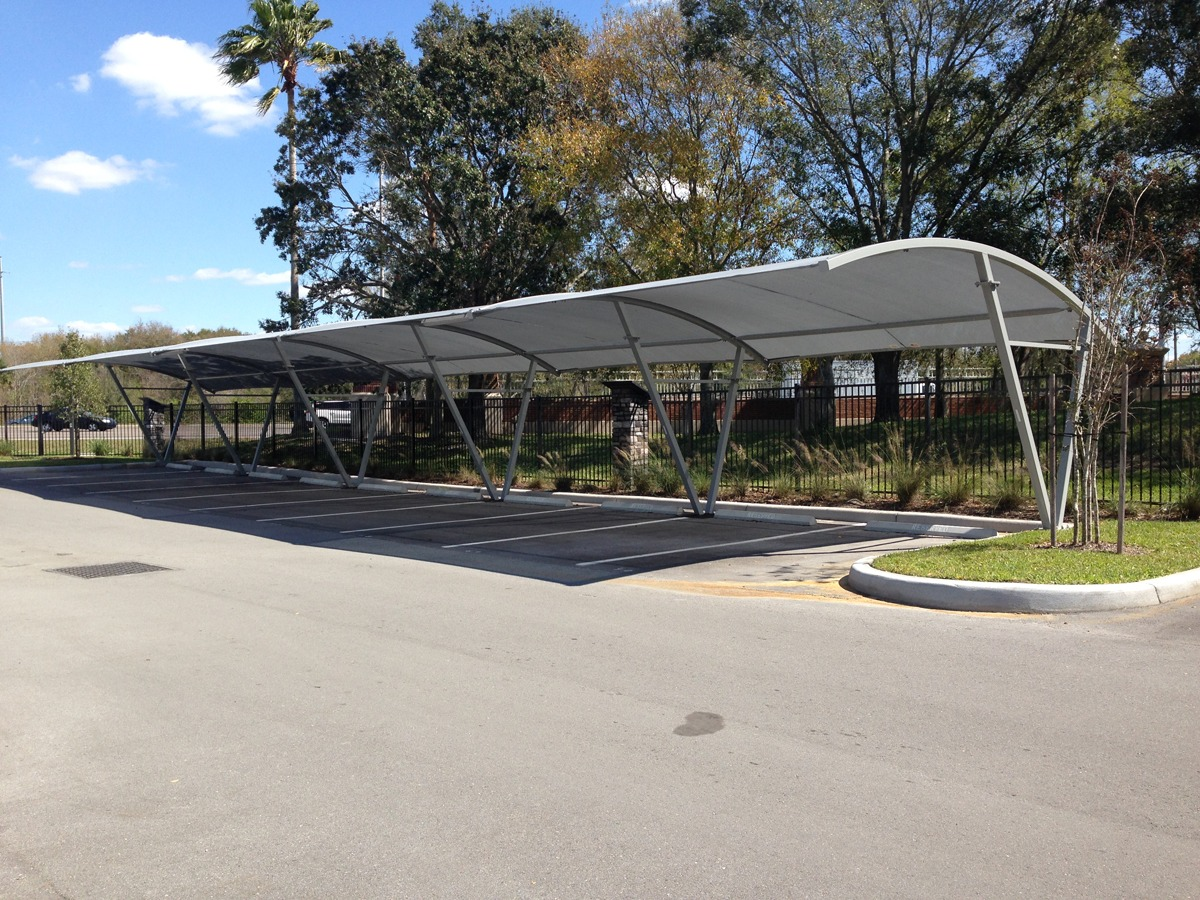 Curved square shade structure over parking lot row.