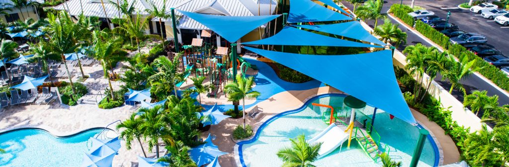 Sail-shaped shade structures covering playground in pool.