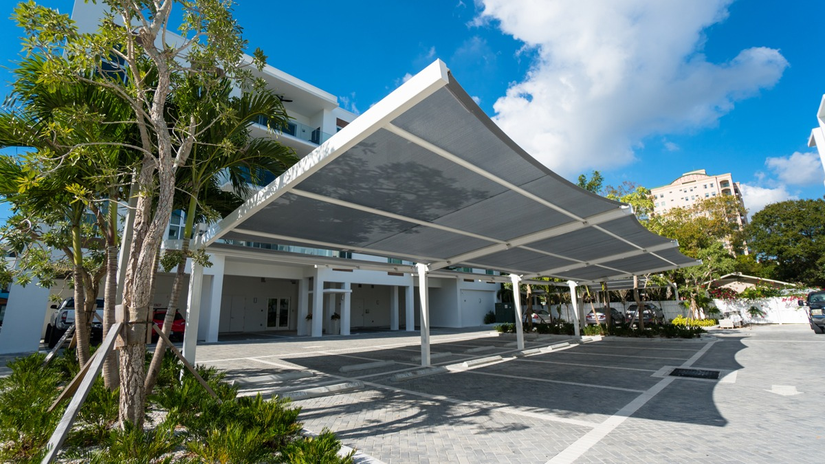 Square shade structure over parking lot row outside apartment complex.