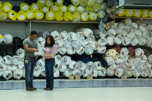 Two Apolo Sunguard team members in front of wall of fabric rolls